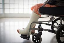 A person sits in a wheelchair, with a cast on their leg