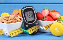 A bowl of cereal, a bowl of strawberries, a blood glucose meter, a tape measure, and free weights