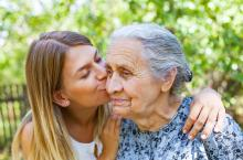 A girl kisses her grandmother on the cheek