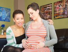 A pregnant woman and her partner sit in a doctor's office