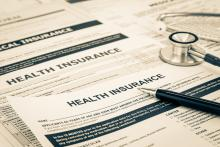 Medical insurance paperwork with a stethoscope on top