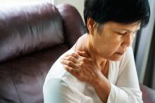 A woman puts her hands on her neck in pain