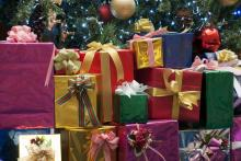 A big pile of brightly wrapped presents under a Christmas tree.