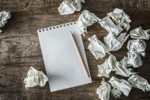Crumpled sheets of paper beside a notebook and pencil