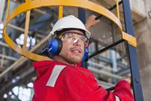 A worker is wearing a hard hat and hearing protection