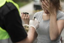 A woman hands her keys to a police officer, looking distraught