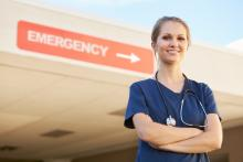 "A doctor stands in front of a sign that says ""Emergency"""
