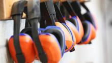 Row of orange protective earmuffs hanging on a rack