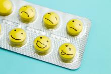 Yellow pills and funny faces in a blister on a blue background.
