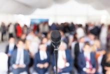 Microphone in front of a conference of people