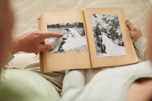 A senior couple looks at an old photo album together
