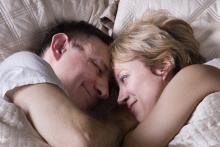 A couple is lying in bed together, snuggling