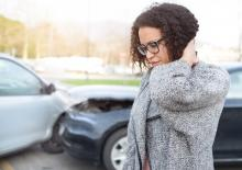 Young woman after being in a collision, holds her neck in pain