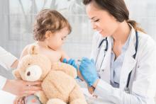 Little girl getting vaccination by female doctor