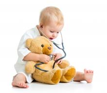Child using a stethoscope and his senses to look after his teddy bear patient