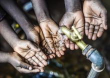 Symbol for fresh water for Africa, sets of hands under fresh pouring water