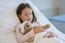 Young girl holding a teddy bear sleeping in a hospital