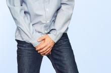 Close up of a man with hands holding his crotch