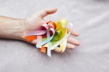 Hand holding all different coloured cancer awareness ribbons