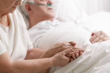 End of life care at a hospice. Married couple with the male hooked up to oxygen