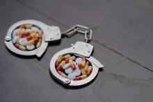 Handcuffs and pills. Selective focus - concept