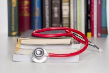 Red stethoscope on top of a pile of books