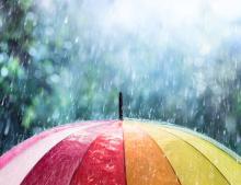 Rain belting down on a rainbow umbrella