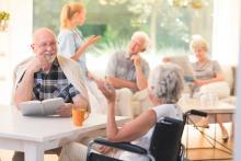 Senior man talking to a senior woman in a wheelchair