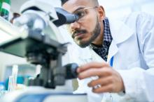 Scientist Using Microscope in Laboratory -