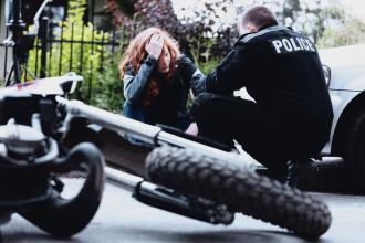 A police officer attends to a woman after a motorcycle accident