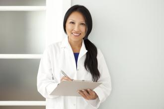 A doctor stands in a hallway, writing on a clipboard