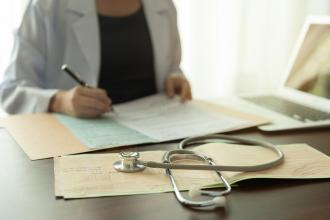 A female doctor sits at a desk, filling out forms, her stethoscope in the foreground.