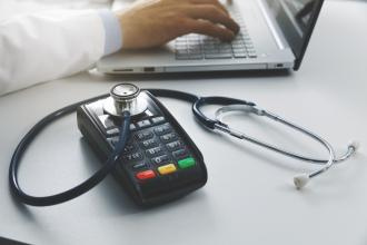 A debit machine sits next to a laptop, with a stethoscope on top of it