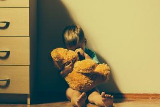 Little boy sitting on floor by dresser hugging a teddy bear and crying