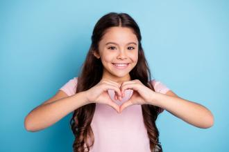 A young girl wears a pink shirt and makes a heart shape with her hands