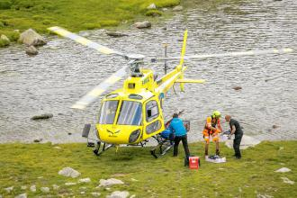 A patient on a stretcher is loaded onto a helicopter