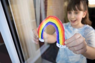 A child holds a drawing of a rainbow up to the window