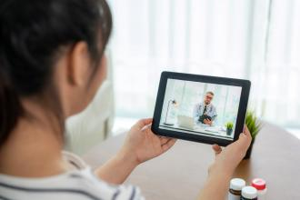 A patient holds an iPad for a virtual medical appointment