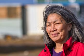An Inuit woman stands outside in a northern community on Baffin Island