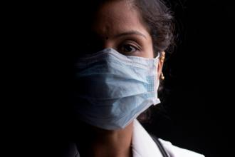 A doctor wearing a mask looks directly into the camera