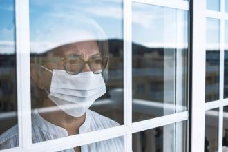 A senior in self-isolation looks out the window