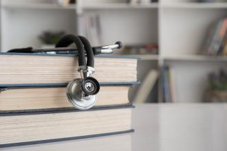 A stethoscope sits on top of a stack of books