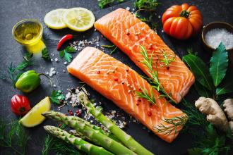 A platter of food typical of a Mediterranean diet: salmon, vegetables, olive oil, and lemons