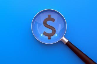 A dollar symbol under a magnifying glass