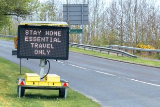 """A digital messaging sign on the side of the road with the words """"Stay home. Essential travel only"""""""