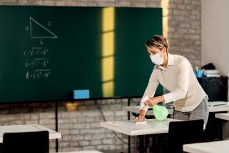 A teacher wearing a mask sanitizes the classroom
