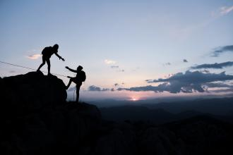 Two silhouettes are seen climbing a mountain; one reaches out a hand to pull the other up