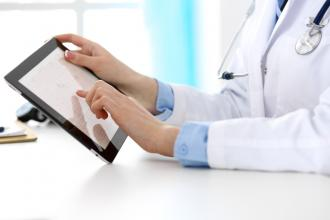 A doctor accesses medical records on a tablet