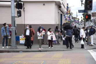 People walking along the sidewalk wearing masks