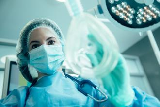 A doctor places an anesthesia mask on a patient